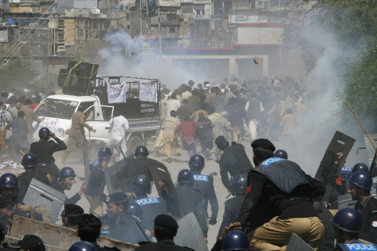 Riot police officers run towards towards protesters during a demonstration against power outage in Muzffarabad, capital of Pakistan-administrated Kashmir. People protesting against power outage in Muzaffarabad turned violent on Thursday. Around 50 people, including a police official, sustained minor injuries when the protesters pelted stones at the police and burnt a police bus, local media reported. (Amiruddin Mughal/Reuters)