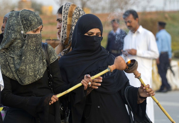 An activist lights her torch as she takes part in a rally to commemorate International Women's Day in Islamabad March 8, 2013. (Mian Khursheed/Reuters)