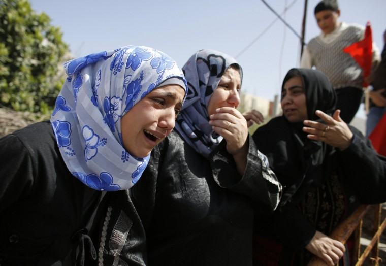 Palestinian women mourn during the funeral of Mahmoud Titi in Fuwar near the West Bank city of Hebron. Israeli troops killed a Palestinian, Titi, on Tuesday during a confrontation with a stone-throwing crowd in a flashpoint district of the occupied West Bank, both sides said. The incident stoked tensions ahead of a visit by U.S. President Barack Obama next week that has been billed as a bid to encourage new peacemaking. (Ammar Awad/Reuters)