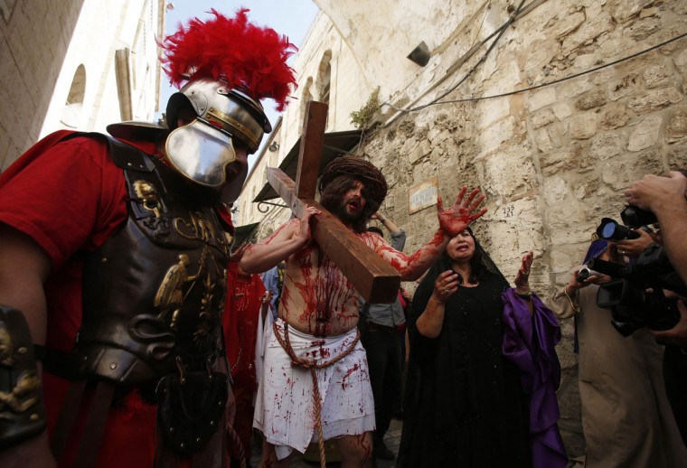 March 29, 2013: A man playing the role of Jesus carries a cross to the Church of the Holy Sepulchre on Good Friday during Holy Week, in Jerusalem's Old City. (Baz Ratner/Reuters)