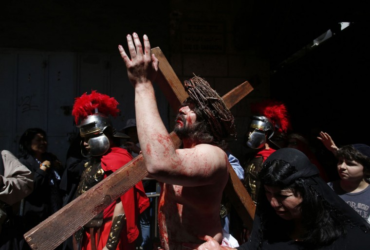 March 29, 2013: A man playing the role of Jesus carries a cross to the Church of the Holy Sepulchre on Good Friday during Holy Week, in Jerusalem's Old City. Christian worshippers retraced the route Jesus took along Via Dolorosa to his crucifixion in the Church of the Holy Sepulchre. (Baz Ratner/Reuters)