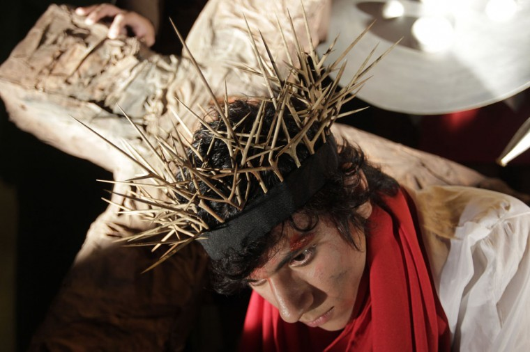 March 27, 2013: An actor carries a cross as he plays the role of Jesus Christ in a re-enactment of the Via Crucis (Way of the Cross) in a procession during Holy Week, in preparation for Good Friday celebrations, in Luque, Paraguay. (Jorge Adorno/Reuters)