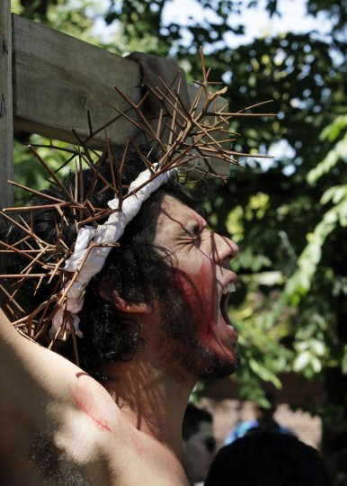 """March 29, 2013: Actor Edrwin Velazquez (on cross) takes part in a """"Via Crucis"""" (Way of the Cross) procession during Holy Week in Yaguaron, 47 km (29 miles) south of Asuncion,Paraguay. (Jorge Adorno/Reuters)"""