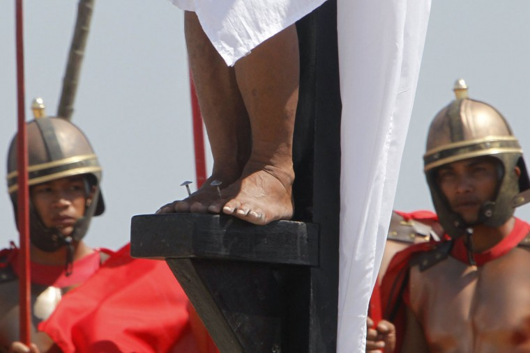 March 29, 2013: Ruben Enaje, 52, who is portraying Jesus Christ for the 27th time, is closely watched by two men who play Roman soldiers while his feet are nailed to a wooden cross during a Good Friday crucifixion re-enactment in San Pedro Cutud town, Pampanga province, north of Manila. (Romeo Ranoco/Reuters)