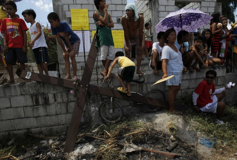 March 29, 2013: Residents stand in front of a wooden cross on which penitent had been hung during a Good Friday crucifixion re-enactment in San Juan village, Pampanga province, north of Manila. About two dozen Filipinos were nailed to crosses on Good Friday in an extreme display of devotion that the Catholic church looks down upon as a form of folk religion but appears powerless to stop. (Romeo Ranoco/Reuters)