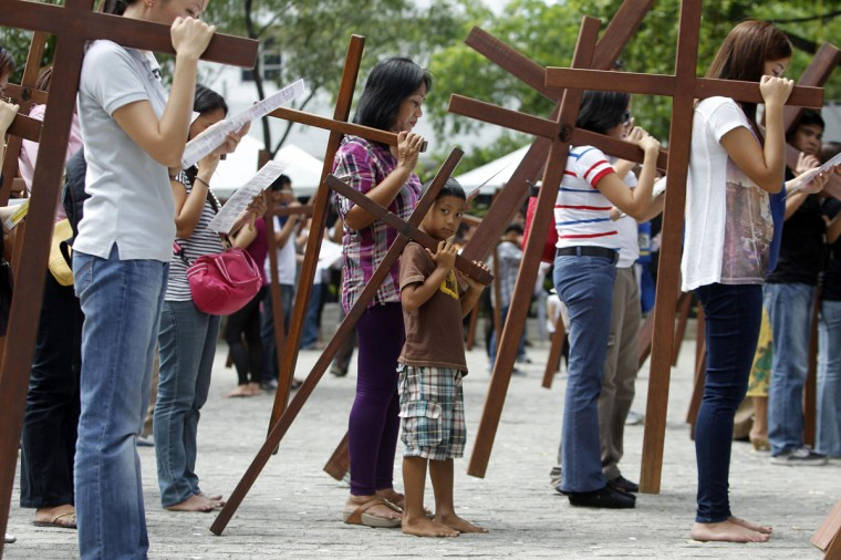 """March 28, 2013: A boy joins his family as they carry crosses to one of the Stations of the Cross while doing the """"Visita Iglesia"""" , a traditional custom of visiting one, seven, or 14 churches and praying on Maundy Thursday, at a church in Quezon City in Metro Manila. (Cheryl Ravelo/Reuters)"""