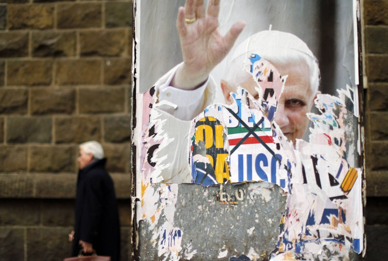 A man walks past a poster of the former Pope Benedict XVI on a board in downtown Rome. With Pope Benedict XVI now officially in retirement, Catholic cardinals from around the world begin on Friday the complex, cryptic and uncertain process of picking the next leader of the world's largest church. (Alessandro Bianchi/Reuters)