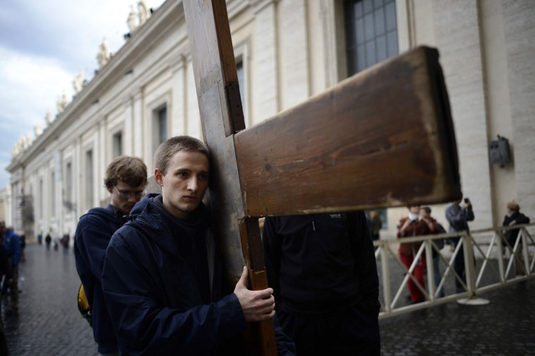 Pilgrims carry a large cross through Saint Peter's Square in the Vatican on March 8, 2013. (Dylan Martinez/Reuters)