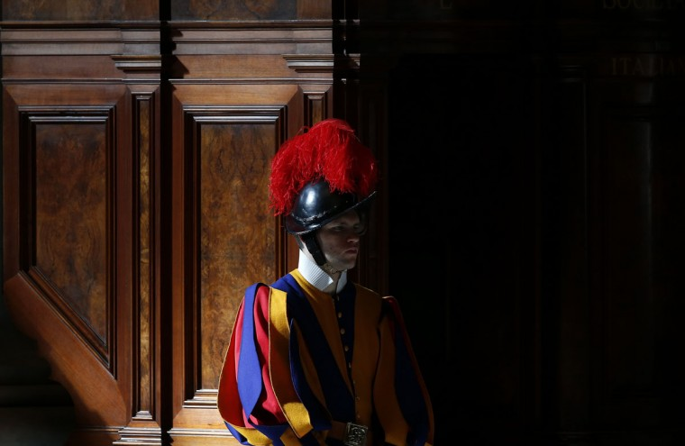 "A Swiss Guard is seen during a mass in St. Peter's Basilica at the Vatican March 12, 2013. All cardinals, including those over 80 who will not vote in the conclave, celebrate Mass in St Peter's Basilica to pray for the election of the new pope. The Mass is called ""Pro Eligendo Romano Pontefice"" (""For the Election of the Roman Pontiff"") and is open to the public. (Stefano Rellandini/Reuters)"