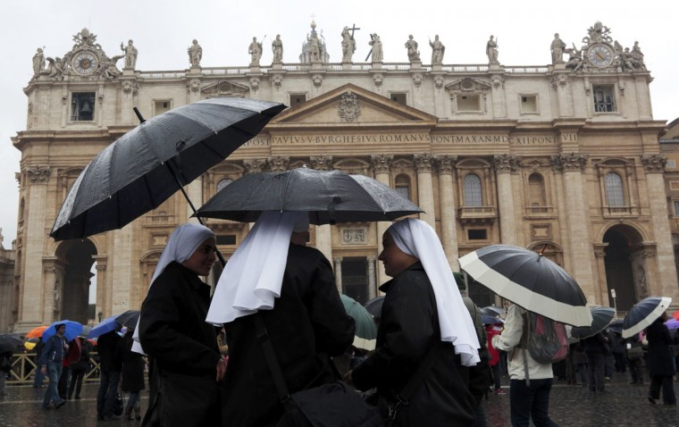 Faithful and nuns shelter from rain while waiting for smoke to rise from a chimney on top of the Sistine Chapel during the second day of voting for the election of a new pope, at the Vatican March 13, 2013. (Eric Gaillard/Reuters)
