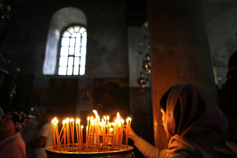 A Christian worshipper lights a candle at the Church of the Nativity, revered as the site of Jesus' birth, in the West Bank town of Bethlehem. Israeli and Palestinian officials welcomed the appointment of the new Pope, on Thursday wishing him success in leading the Catholic Church. (Ammar Awad/Reuters photo)
