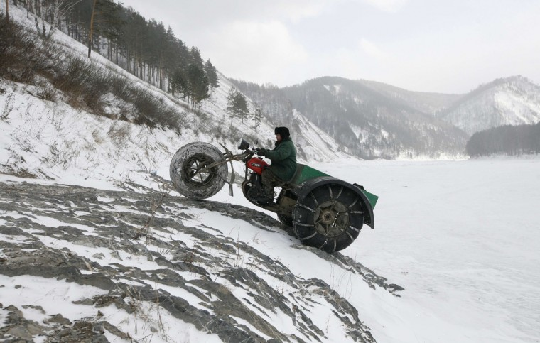 """Alexander Yushkov, 49, a boiler room operator in a local mining company, drives his self-made three-wheeled cross-country vehicle called """"Bolivar"""" near the frozen Mana river in a remote taiga area, some 60 km (37 miles) southeast of Russia's Siberian city of Krasnoyarsk. Yushkov created the vehicle for off-road travel across the taiga through all possible weather conditions by modifying and reconstructing a 1971 Soviet made """"Izh Planeta"""" motorcycle. (Ilya Naymushin/Reuters)"""