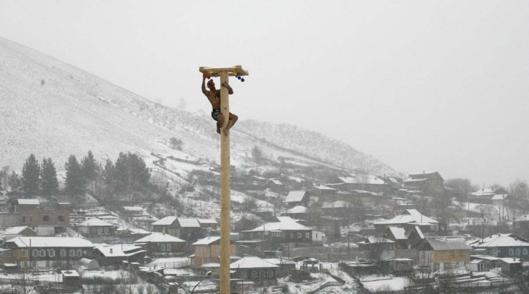 A man climbs up a smooth wooden column to win a contest during the celebrations of Maslenitsa, or Pancake Week, at the Bobrovy Log ski resort on the surburbs of Russia's Siberian city of Krasnoyarsk, March 17, 2013. Maslenitsa is widely viewed as a pagan holiday marking the end of winter and is celebrated with pancake eating, while the Orthodox Church considers it as the week of feasting before Lent. (Ilya Naymushin/Reuters)