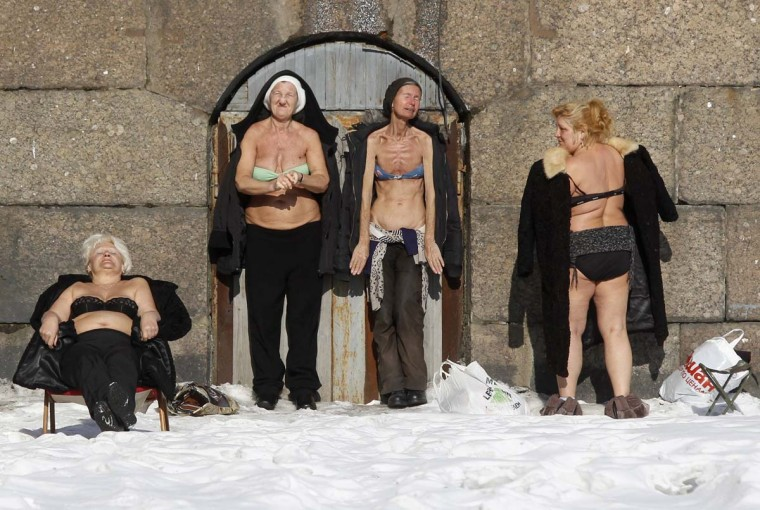 People sunbathe by the wall of the Peter and Paul Fortress in St. Petersburg March 10, 2013. (Alexander Demianchuk/Reuters)