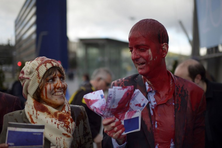 Members of pacifist group Platform Against The BBVA, covered in red paint to symbolise investments in armaments, hold up euro notes and bank books before the Annual General Meeting of Shareholders of Spain's second biggest bank BBVA, at the Palacio Euskalduna in Bilbao. (Vincent West/Reuters)