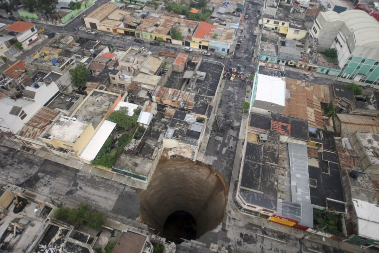 A giant sinkhole caused by the rains of Tropical Storm Agatha is seen in Guatemala City on May 31, 2010. More than 94,000 people were evacuated as the storm buried homes under mud, swept away a highway bridge near Guatemala City and opened up sinkholes in the capital. (Casa Presidencial / Handout / Reuters)