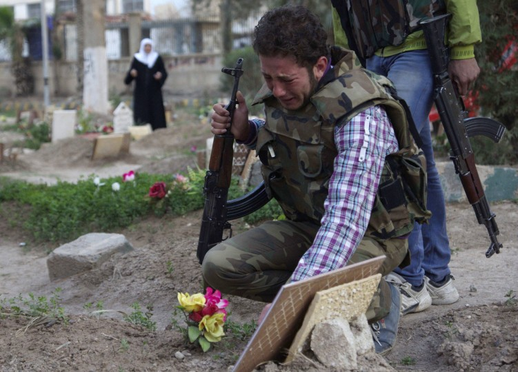 A Free Syrian Army fighter mourns at the grave of his father who was killed by what activists said was shelling by forces loyal to Syria's President Bashar al-Assad, in a public park that has been converted into a makeshift graveyard in Deir el-Zor. (Khalil Ashawi/Reuters)