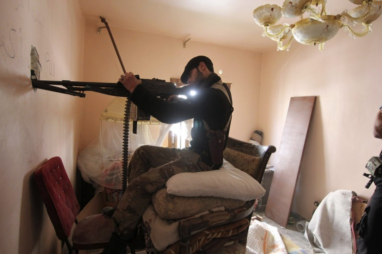 A Free Syrian Army fighter takes position inside a room as he points his weapon through a hole in Aleppo's Saif al-Dawla district. (Giath Taha/Reuters photo)