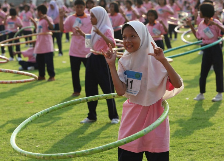 February 12, 2013: People take part in an attempt to break the Guinness world record for most number of people simultaneously hula-hooping at Thammasat University stadium in Pathum Thani province, on the outskirts of Bangkok. Thailand broke the previous record held by Taiwan, with a new record of 4483 people hula-hooping for 7 minutes. The event was organized by the public health ministry to promote exercise and good health. (Kerek Wongsa/Reuters)