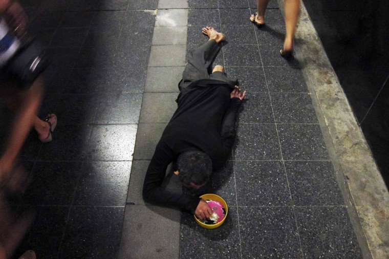 A disabled man begs as people pass by in Bangkok's shopping district March 18, 2013. (Damir Sagolj/Reuters)