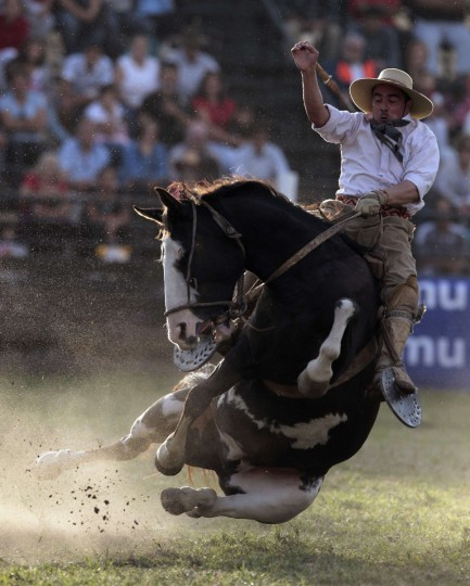"""A gaucho rides an unbroken horse during the annual celebration of Criolla Week in Montevideo. Throughout Easter Week """"gauchos"""", the Latin American equivalent of the North American """"cowboy"""", from all over Uruguay and neighboring Argentina and Brazil visit Montevideo to participate in Criolla Week to win the award of best rider. The competition is held March 24 - March 30. (Andres Stapff/Reuters)"""