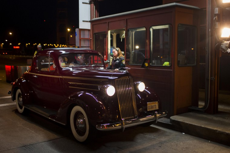 Toll collector Marilyn Alvarado (R) receives the last toll from Jim Eddie (C), who is driving a vintage 1937 Packard, at her tollbooth at the Golden Gate Bridge toll plaza in San Francisco, California. The Golden Gate Bridge will convert from manned tollbooths to a full electronic tolling system starting March 27. With the automated system in place, motorists will have the option of using the existing FasTrak electronic toll collection system or the newly implemented pay-by-plate option, according to Golden Gate Bridge management. (Stephen Lam/Reuters)