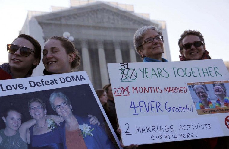 Jo-ann Shain (R) and Mary Jo Kennedy (2nd from R) and Shain's daughter, Aliya Shain, 24, and Aliya's girlfriend, Brianna Clark (L), from Brooklyn, New York, hold signs as they stand outside of the U.S. Supreme Court in Washington, March 26, 2013. (Jonathan Ernst/Reuters)