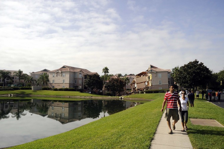 Tourists walk past a section of the Summer Bay Resort after a large sinkhole opened on the property's grounds, in Clermont, Florida August 12, 2013. Dozens of guests at the Florida resort near Walt Disney World were evacuated early Monday, when at least two buildings partially collapsed due to the sinkhole, guests and resort employees said. (David Manning/Reuters photo)