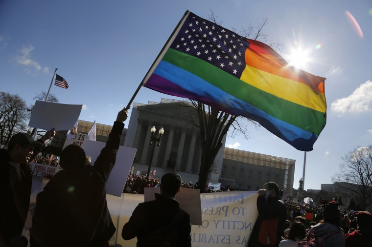 Anti-Proposition 8 protesters wave a rainbow flag in front of the U.S. Supreme Court in Washington. Two members of the U.S. Supreme Court, both viewed as potential swing votes on the right of gay couples to marry, raised doubts about California's gay marriage ban on Tuesday as they questioned a lawyer defending the ban. (Jonathan Ernst/Reuters)