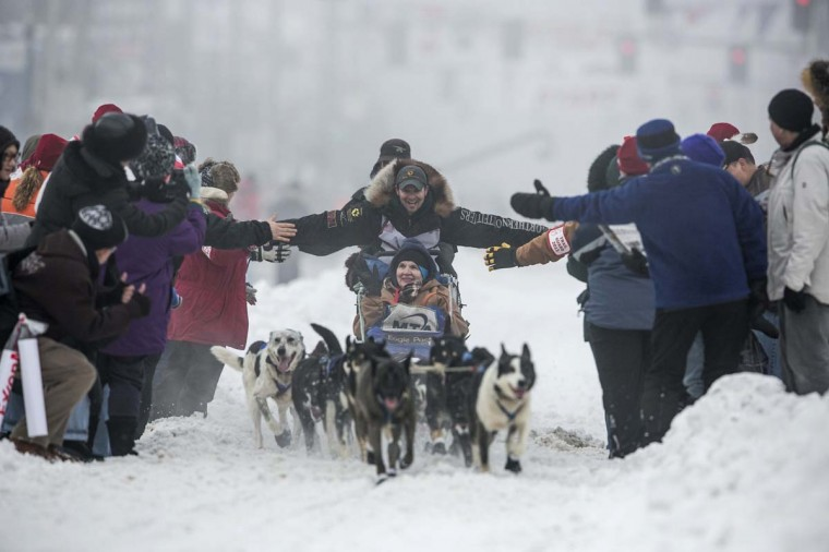 Musher Matt Failor greets spectators as he races down 4th Avenue at the ceremonial start to the Iditarod dog sled race in downtown Anchorage, Alaska March 2, 2013. (Nathaniel Wilder/Reuters)