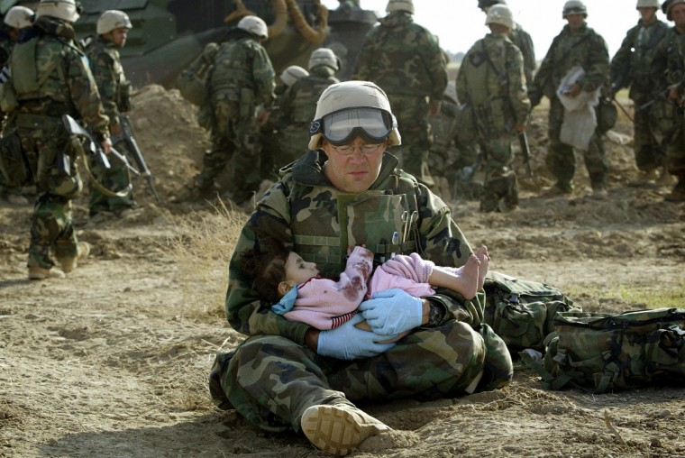 U.S. Navy Hospital Corpsman HM1 Richard Barnett, assigned to the 1st Marine Division, holds an Iraqi child in central Iraq in this March 29, 2003 file photo. Confused front line crossfire ripped apart an Iraqi family after local soldiers appeared to force civilians towards positions held by U.S. Marines. March 20 marks the one year anniversary of the beginning of the U.S. led war against Iraq. The war started on March 20 Baghdad local time, March 19 Washington D.C. local time. (Damir Sagolj/Reuters photo)