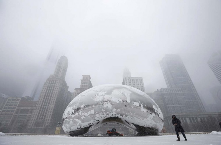 "A woman walks by the Cloud Gate Sculpture, known as ""The Bean"", as a snow plow clears the area during a snowstorm in Chicago March 5, 2013. A deadly late winter storm dumped heavy snow on the Midwestern United States on Tuesday, contributing to numerous highway crashes and flight cancellations as it moved east toward the Ohio Valley and the mid-Atlantic states. (Jim Young/Reuters)"
