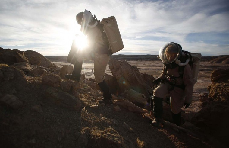 Melissa Battler (L), a geologist and commander of the Crew 125 EuroMoonMars B mission, and Csilla Orgel, a geologist, climb a rock formation to collect geologic samples for study at the Mars Desert Research Station (MDRS) in the Utah desert March 2, 2013. (Jim Urquhart/Reuters)