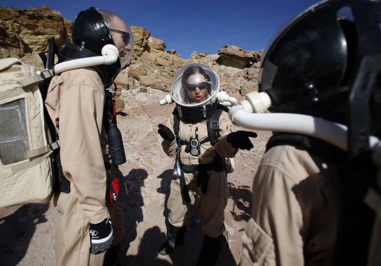 Melissa Battler (C), a geologist and commander of Crew 125 EuroMoonMars B mission, talks to members of the crew about collecting geologic samples for study at the Mars Desert Research Station (MDRS) in the Utah desert March 2, 2013. (Jim Urquhart/Reuters)