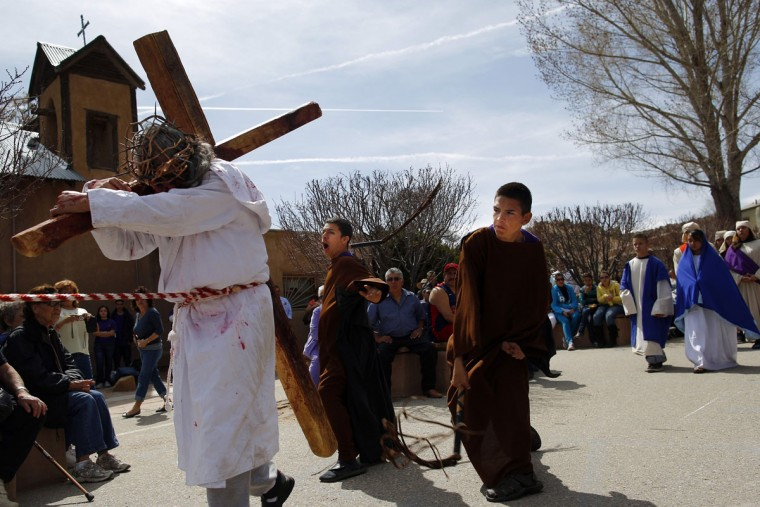March 28, 2013: Students playing the roles of Roman soldiers flog a man playing the role of Jesus (L) during a re-enactment of the Stations of the Cross at the Sanctuary of Chimayo in Chimayo, New Mexico. The students are part of a youth group from Our Lady of Sorrows church in Bernalillo, New Mexico which re-enacts the Stations of the Cross every year. (Brian Snyder/Reuters)