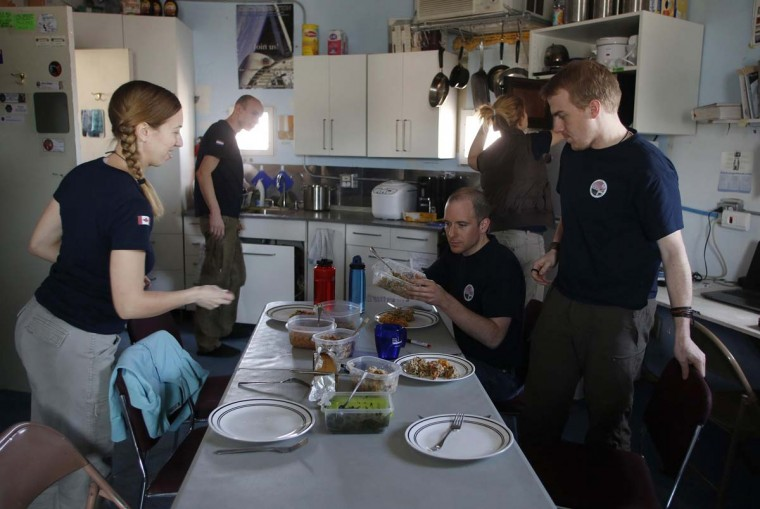 Members of Crew 125 EuroMoonMars B mission prepare a meal at the Mars Desert Research Station (MDRS) outside Hanksville in the Utah desert March 2, 2013. They live together in a small communication base with limited space and supplies. (Jim Urquhart/Reuters)