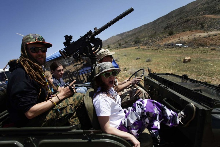 Danny Josephson (L) and his wife Jesse (R) ride in his father Kent Josephson's 1953 Willys Jeep with a Browning .30 caliber machine gun attached at the center during the Big Sandy Shoot in Mohave County, Arizona, March 23, 2013. The Big Sandy Shoot is the largest organized machine gun shoot in the United States attended by shooters from around the country. Vintage and replica style machine guns and cannons are some of the weapons displayed during the event. Picture taken March 22, 2013. (Joshua Lott/Reuters)