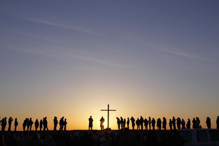 People are silhouetted as the sun rises during an Easter sunrise service in Scituate, Massachusetts March 31, 2013. (Jessica Rinaldi/Reuters)