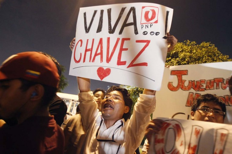 Peru's supporters of Venezuelan President Hugo Chavez shout slogans while gathering outside Venezuela's embassy in Lima after the announcement of his death, March 5, 2013. Chavez died on Tuesday after a two-year battle with cancer, ending 14 years of divisive rule. (Enrique Castro-Mendivil/Reuters)