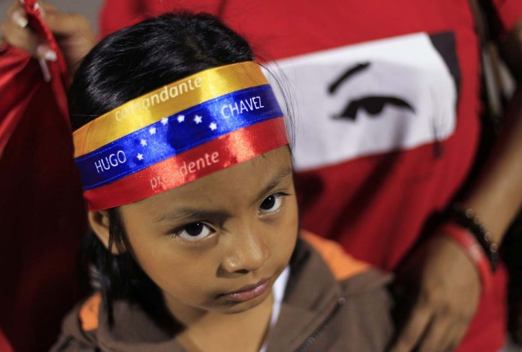 "A young supporter of Venezuela's President Hugo Chavez wears a headband that reads ""Commander Hugo Chavez, President"" while standing at a square in San Salvador March 5, 2013. Chavez died on Tuesday after a two-year battle with cancer, ending 14 years of tumultuous rule that made the socialist leader a hero for the poor but a hate figure to his opponents. (Ulises Rodriguez/reuters)"