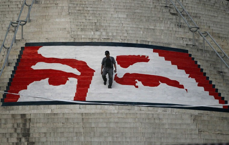 "A man walks at the steps to a monument painted with the likeness of Venezuela's late President Hugo Chavez, as his body lies in state at the military academy in Caracas March 8, 2013. Chavez will be embalmed and put on display ""for eternity"" at a military museum after a state funeral and an extended period of lying in state, acting President Nicolas Maduro said on Thursday. (Jorge Dan Lopez/Reuters)"