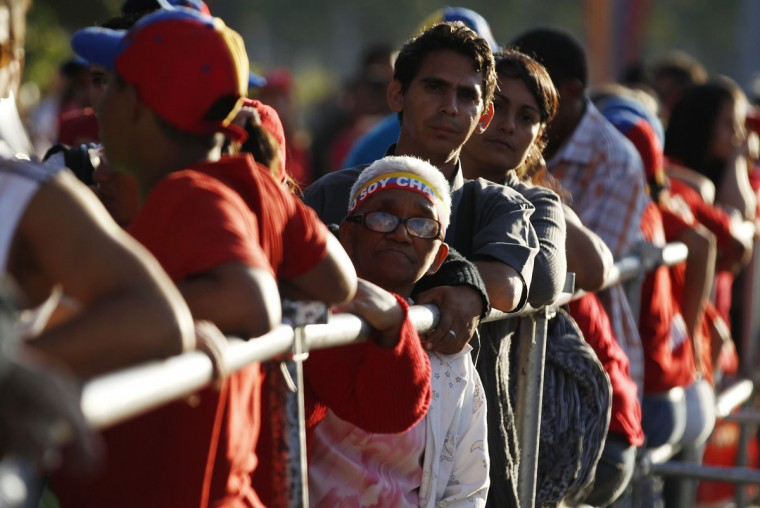 "Supporters of Venezuela's late President Hugo Chavez wait for a chance to view his body lying in state, at the military academy in Caracas March 8, 2013. Chavez will be embalmed and put on display ""for eternity"" at a military museum after a state funeral and an extended period of lying in state, acting President Nicolas Maduro said on Thursday. (Tomas Bravo/Reuters)"
