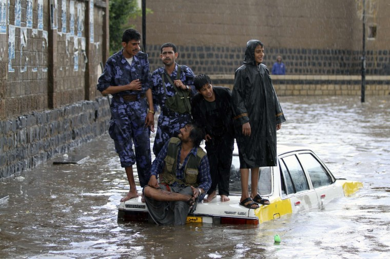 Policemen (L and 2nd L) stand on a car on a flooded street following heavy rains in Sanaa, Yemen. (Mohamed al-Sayaghi/Reuters photo)