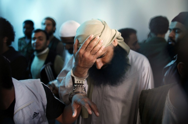 A suspected al Qaeda militant holds his head as he stands with co-defendants behind bars at the state security court of appeals in Sanaa. The court on Tuesday upheld jail sentences ranging from four to 10 years against 10 defendants convicted of having links to al Qaeda, the state Saba news agency reported. (Khaled Abdullah/Reuters)