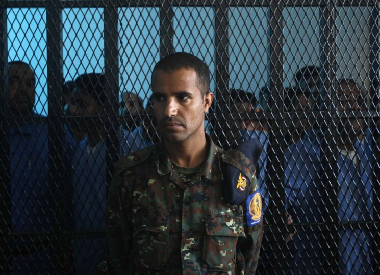 A police trooper stands guard as defendants Abdulkarim Lalji (L) and Hani Ahmad Mohammad (2nd L), convicted of spying for Iran, stand with other defendants behind courtroom bars at a state security court of appeals in Sanaa March 25, 2013. The court on Monday commuted the death sentences of Lalji and Mohammad to five years in prison. The pair were convicted in 2009 of providing the Iranian Embassy in Yemen with military information, according to the Yemen News Agency (SABA). (Khaled Abdullah/Reuters)