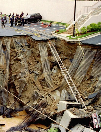 Atlanta police and firefighters secure an area where an enormous sinkhole over a hundred feet in diameter in the parking lot of a Marriott Courtyard hotel collapsed by a break in a sewage culvert on June 14, 1992. The incident, which claimed at least one life, occurred after heavy rain fell through the night. (John Kuntz/Reuters)