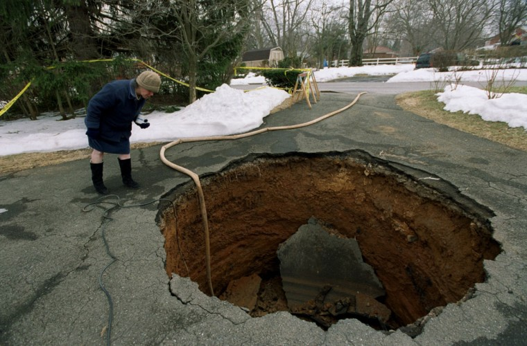 A Lochearn woman peers into an approximately 10 foot by 10 foot sinkhole that appeared in her driveway in March 2003. In the photo, a pump is removing water from the hole. (Kim Hairston/Baltimore Sun Photo)