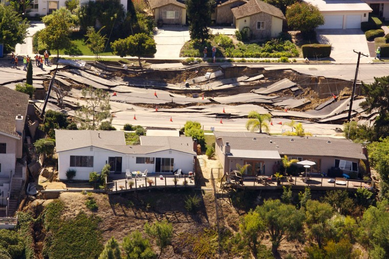 A massive sinkhole, approximately 200 feet by 240 feet, opens up and tears apart the pavement of Soledad Mountain Road, October 3, 2007 in the Mount Soledad neighborhood of La Jolla near San Diego, California. The landslide damaged or destroyed reportedly 6 homes and forced the evacuation of at least 20 others. (Kent Horner/Getty Images)