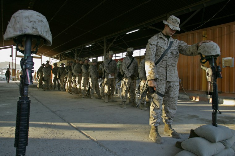 US marines from 2nd Battalion, 2nd Marines Regiment respect to two fallen colleagues that were killed recently during a memorial ceremony held at their headquarters, in the outskirts of Fallujah, west of Baghdad, 10 December 2005. In one of the US military deadliest attacks in Iraq in recent months, ten marines were killed and 11 wounded 01 December in a roadside bomb outside Fallujah. According to the last update on the Pentagon website, 2,138 US military personnel have been killed in Iraq since the 2003 US-led invasion. (Mauricio Lima/Getty Images)