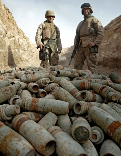 Marines stand over a pile of unused ordinance in the restive city of Fallujah, west of Baghdad. Marines found the rounds after seraching throughout a deserted Iraqi dump site. UN Secretary General Kofi Annan flew in to Baghdad on a surprise visit 12 November 2005. It is Annan's first visit to Iraq since US-led invasion forces ousted former dictator Saddam Hussein in April 2003. (USMC/Lance CPL. Joel Abshier/via Getty Images)